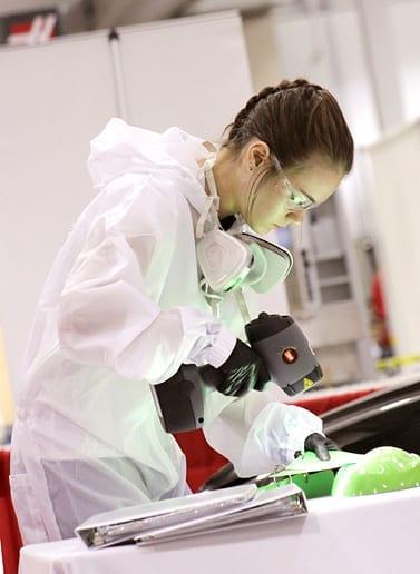 Ashley Weber à l'œuvre durant une épreuve de peinture automobile aux Olympiades canadiennes des métiers et des technologies.